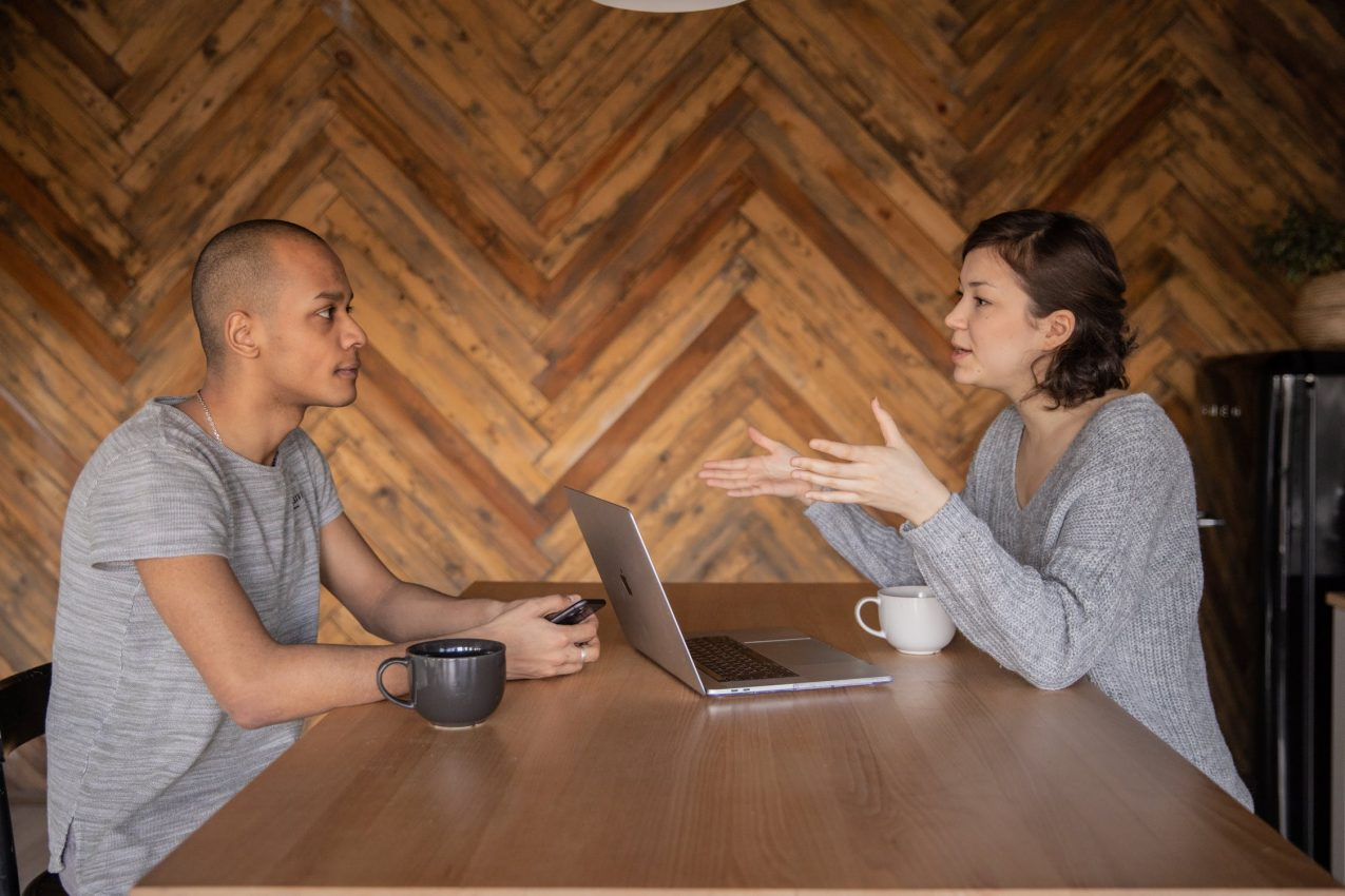 Man and woman both in grey discussing work at a wooden table