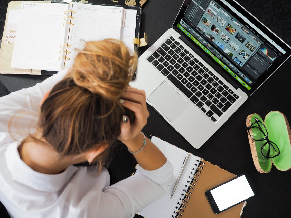 Woman looking stressed while sitting at her desk