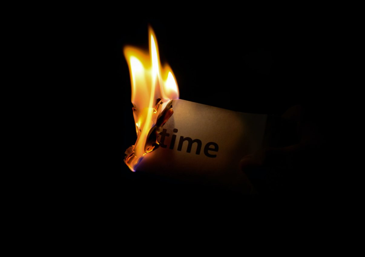 Piece of paper with the word time written on it burning
